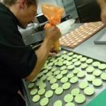 Michel inserisce il ripieno nei macarons
